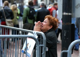 A woman kneels and prays at the scene of the first explosion on Boylston Street near the finish line of the Boston Marathon on April 15. (Credit: Getty Images)